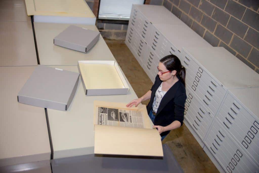 This is a photograph of an archivist looking for specific media in Subaru's company archives.