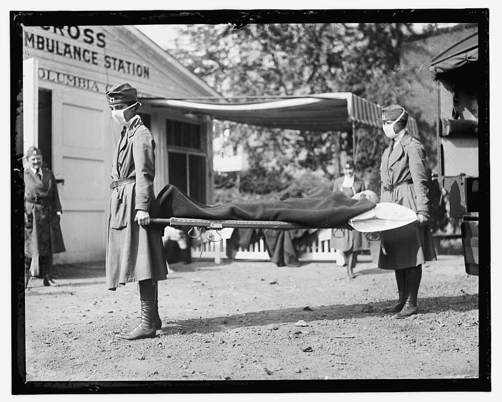 Pictured: Two medical workers carrying a body during a pandemic.